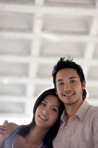 79395890-asian-couple-hugging-gettyimages